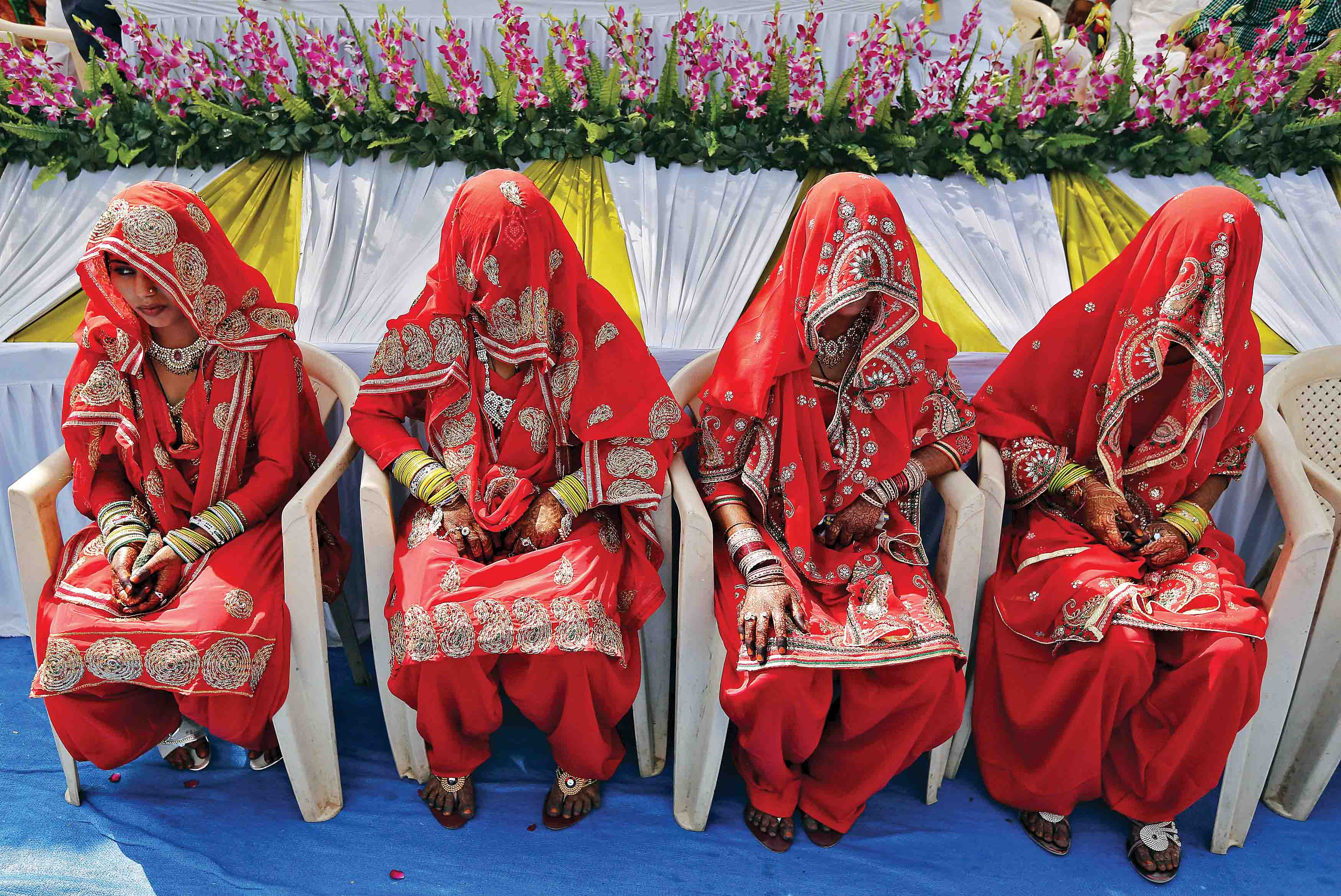 Muslim brides sit as they wait for the start of a mass marriage ceremony in Ahmedabad